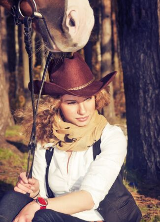 Cute cowgirl with her red horse.