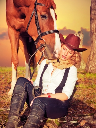 Beautiful  cowgirl with her red horse Stock Photo