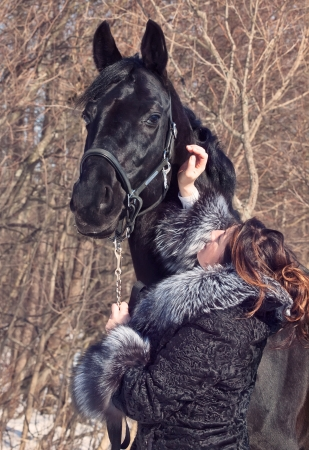 women with black horse at forest background.spring photo