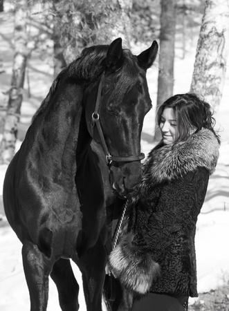 nice women with black horse portrait. photo