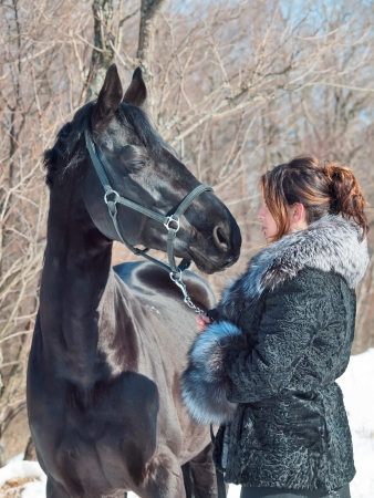 women with black horse. winter photo