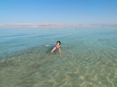 Woman swimming in salty water of a Dead Sea photo