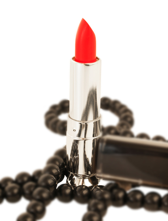 pomatum: Red lipstick and black bead over white background Stock Photo