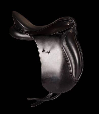 stirrup: Black leather premium dressage saddle isolated at black background