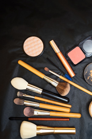 Set of make up brushes  with makeup products on black background