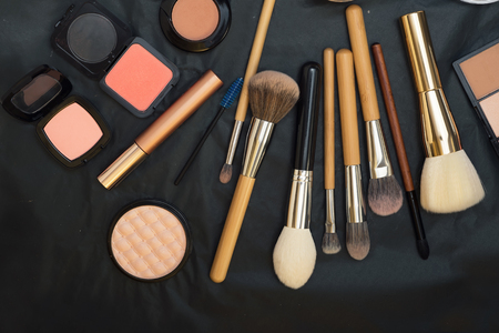 Set of make up brushes  with cosmetics on black background