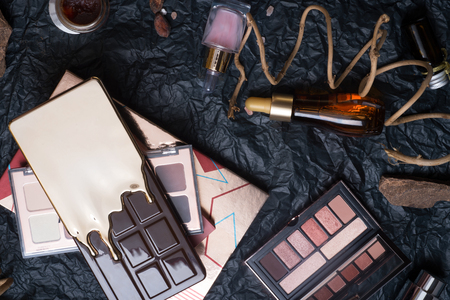 set of eye shadow palettes, cosmetics  and nature chocolate on black background  in frame . 스톡 콘텐츠