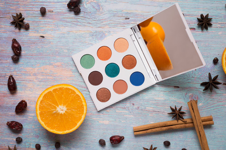 fashion summer eye palettes with  fruit and spices at blue wooden background. close up