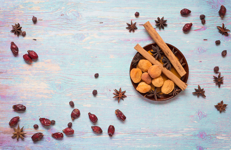 blue wooden background with cinnamon, anise, dog rose  and dried apricots Stockfoto