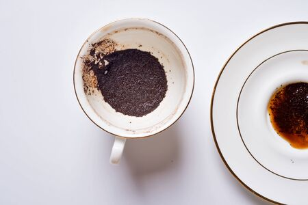 Divination on coffee grounds in white cup and plate around white