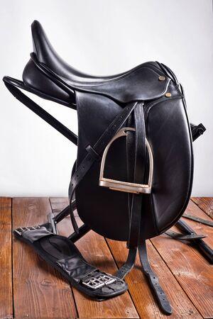 Black professional  leather dressage saddle with stirrups Stock Photo