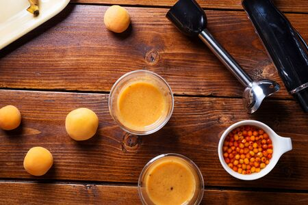 Blender laying at a wooden table with a fresh fruit smoothie with bananas, sea buckthorn, and apricots.  Flat lay