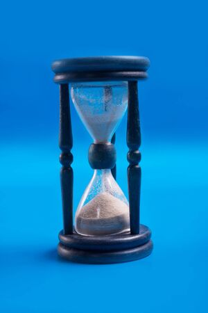 blue hourglass over bluebackground. close up