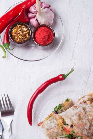 international vegetarian  shawarma sandwich roll with chili and spices. served at white table. arabian and caucaisian cuisine. Healthy fast food. flat lay