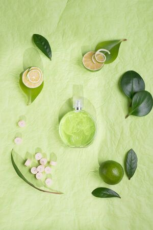 perfume bottle around ingredients  background on green background Stock Photo