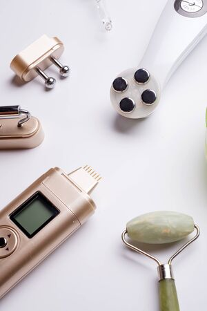set of different hardware equipment with vacuum jars, nephrite roll and massage brush. anti-age and anti-cellulite set for home skin care procedure. beauty concept. close up