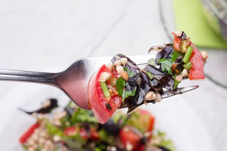 fork with vegetarian fresh salad with vegetables, herbs and  sprouts  of buckwheat.  beautiful served in transporant bowl at white table. healthy raw eating food. close up