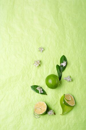 limes with leaves and flowers   on green background. flat lay. copy space 写真素材