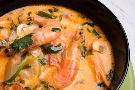 famous delicious Thai Tom yum spicy soup with shrimps and coconut milk on black table. close up Reklamní fotografie