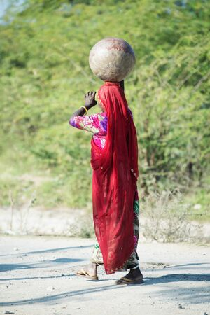 traditionally dressed woman in traditional indian Saree walking at rural road with pot at head. Rajasthan. India
