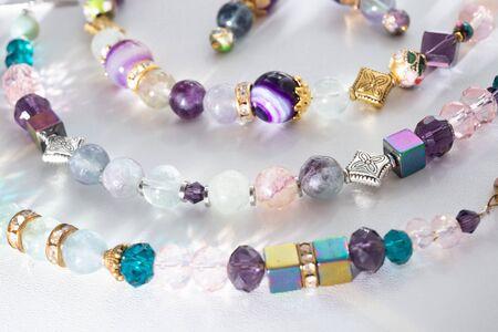 Pulseras de joyería de oro con cristal y semipreciosos en fondo blanco.