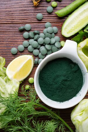 spirulina powder around green fresh vegetables. served at woodentable