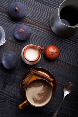 coffee with natural cream and tasty ripe purple fig on black wooden table. flat lay 写真素材