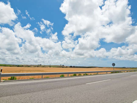 view of green rural area with road part against clouds sky. Spain, Andalusia