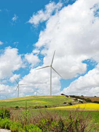view of green rural area with windmills turbines against clouds sky. Spain, Andalusia