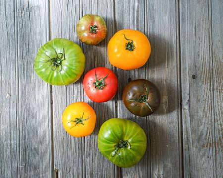 木製の背景にカラフルな家宝のトマト。 写真素材