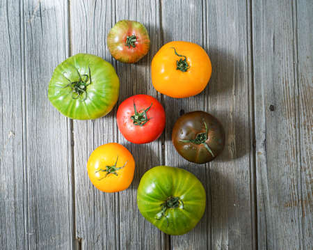 colorful heirloom tomatoes on wooden background.