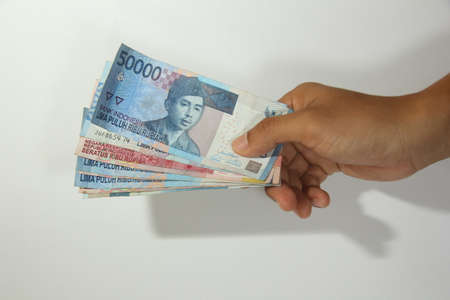 hands giving out fifty thousand money on white background, rupiah money, hand showing 50000 rupiah money