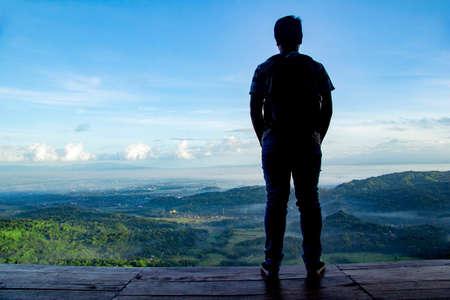 schöne Landschaftsansicht vom Becici Pine Peak auf Yogyakarta, einsamer Mann steht im Holzboden mit schöner Aussicht auf Standard-Bild
