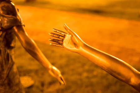 A fragment, the hand of a statue, a bronze hand reaching out to another person, palm. Concept. Night time