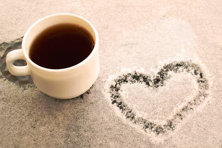 White cup of coffee on a snow covered table. Figure in the form of a heart. Romantic morning at the resort in the winter.