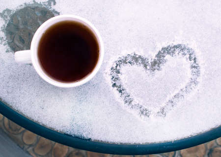 White cup of coffee on a snow covered table. Romantic morning at the resort in the winter. Banco de Imagens