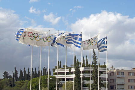 National flags of Greece and the Olympic Games next to the National Olympic Stadium in the center of Athens. Flagpoles flying in the wind flags in Athens Redactioneel