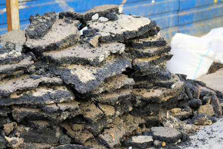 Pieces of old asphalt closeup. Layers of shot asphalt piled on top of each other. Road robots.