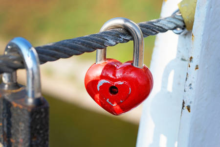 Red lock hang on a cable on a bridge. Symbol of eternal love and fidelity metal heart-shaped lock on the bridge close-up. Wedding traditions.