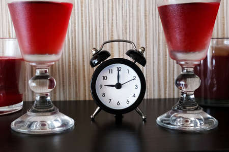 Romantic setting an appointment on Valentine's Day. Two glasses with red cold wine and a black small alarm clock in the center. Be late for a date, do not come at the appointed time.
