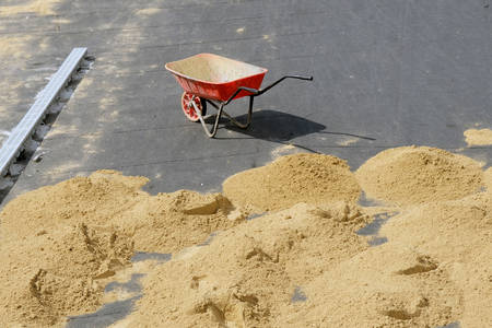 Red wheelbarrow with one wheel on the pavement and many small slides of sand on the ground. Improve road paths in the city, work outside on a hot sunny day. 写真素材