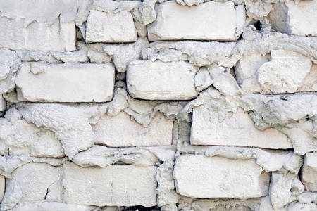 Rugged brick wall with pieces of cement background. A fragment of a brick fence where a thick layer of cement and unevenly stacked stones.