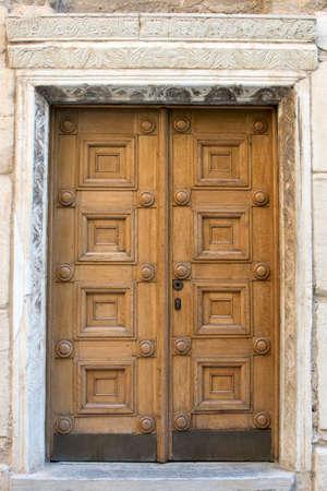 Vintage beautiful wooden door with carved elements. Large massive front door to the building. Closed entrance double doors. Stock fotó