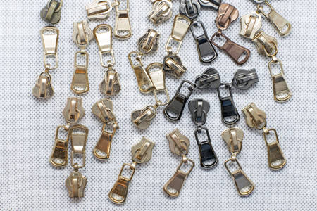 Metal zipper for clothes, bags or shoes. Fittings for making wallets of gold and black color. zipper sliders on a white background.