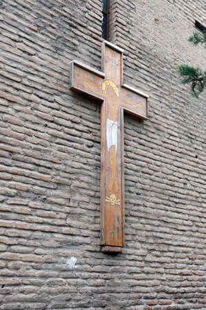 Natural wooden cross on a brick wall. Cross on the wall of an ancient temple, side view. The concept of religion and a symbol of Christianity.