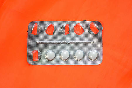Gray blister with white pills on an orange background. Half empty pack with pills. Round white allergy pills.