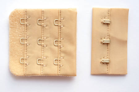 Hooks and loops for a bra on a beige piece of fabric. Metal fasteners for women's underwear. Accessories for sewing bra loops and fasteners.