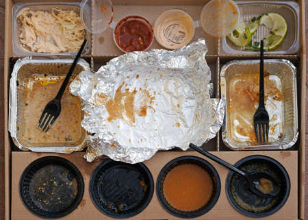 Box of fast food, empty plates with forks, sauces and aluminum bowls top view. Used plastic dishes are dirty after eating in a cardboard box. Home delivery Mexican food.
