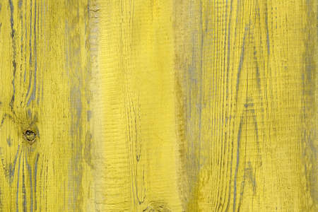 Brightly yellow painted paint board close-up. Wooden surface with texture top view. Perfect as a background for Summer Holiday or seaside themes.