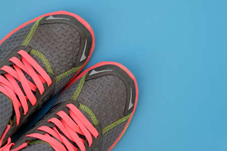 Gray sneakers with pink laces on a blue background top view. Textile sneakers with colorful laces and pink soles. The concept of an active lifestyle, sports, competitions. Copy space Stock Photo